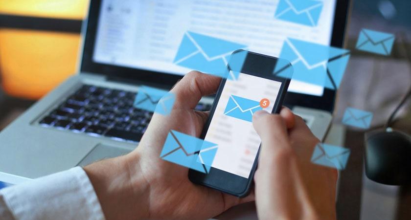 Hände halten ein Handy, dessen Bildschirm ein E-Mail Icon enthält. Im Hintergrund ist ein Notebook.